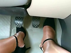 crossdresser driving car in high heels and glossy pantyhose